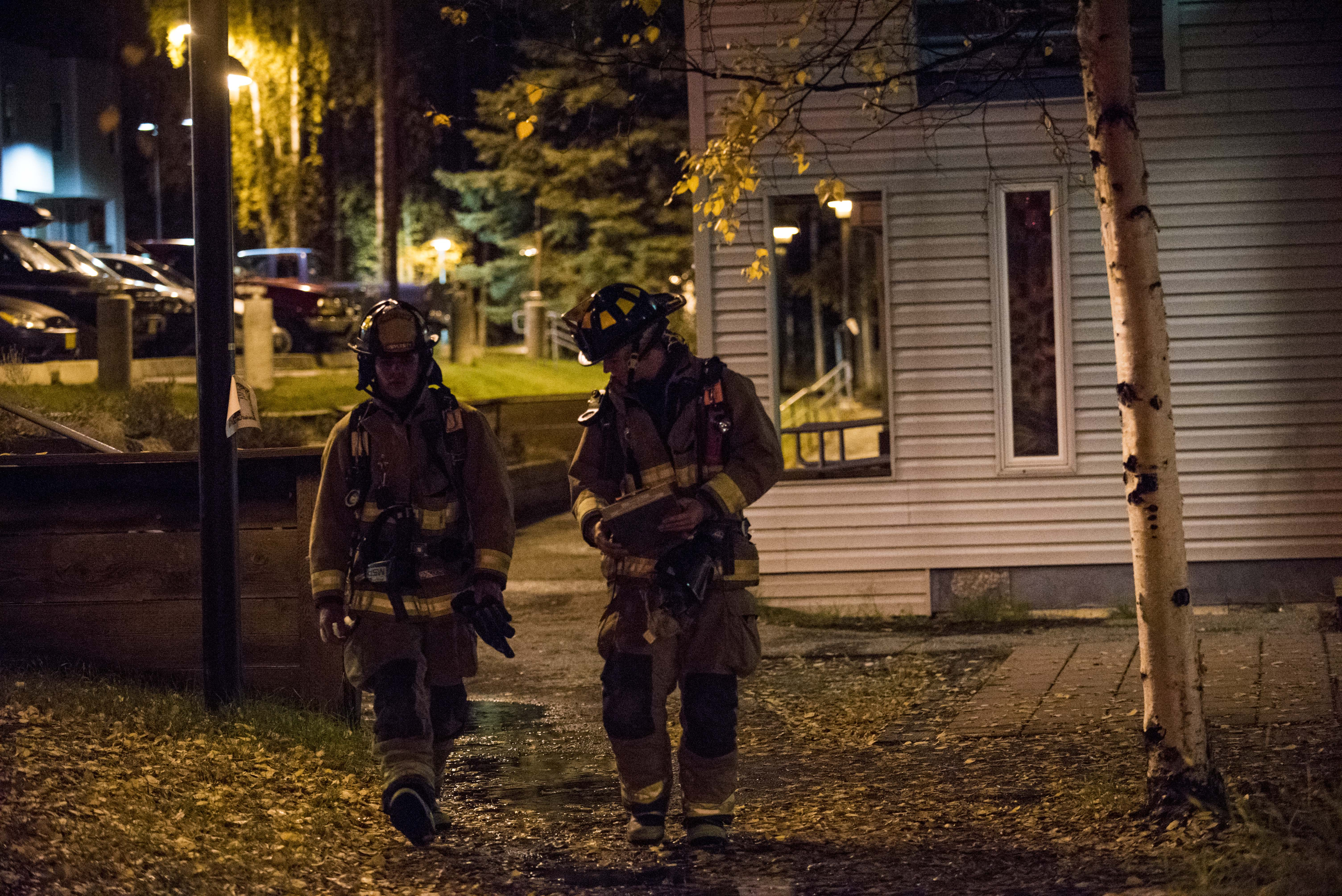 Two firefighters walk back towards their firetruck following a false alarm on Sep. 17 in the Cutler Apartments. - Zayn Roohi / Photo Editor